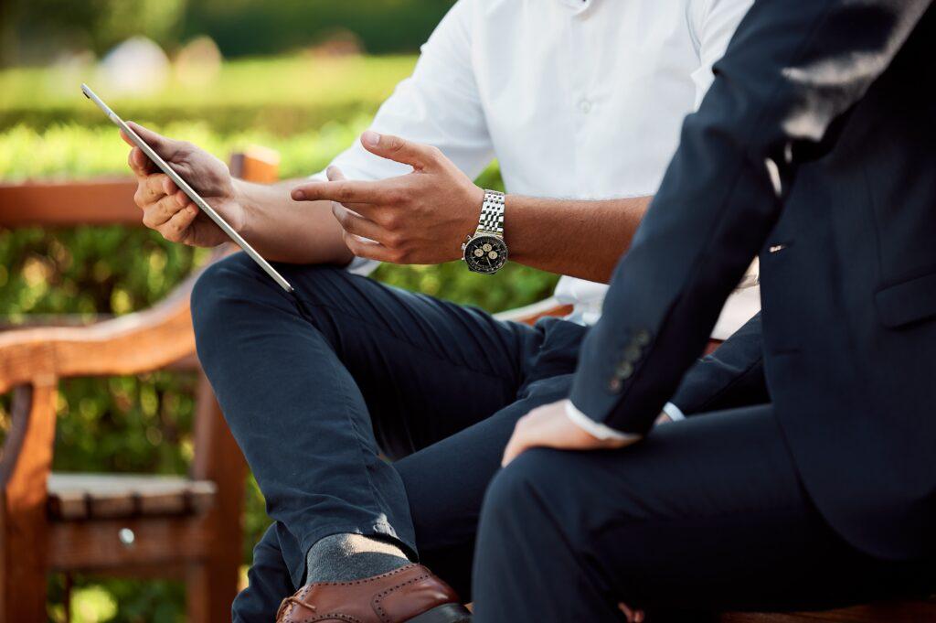 un homme présentant à l'aide de la tablette tactile à un autre homme